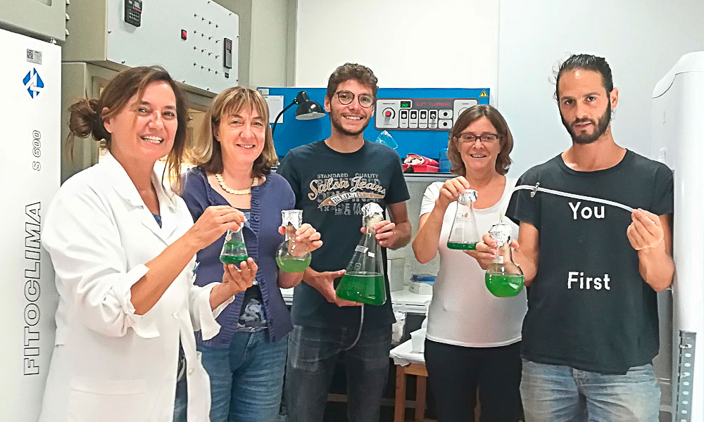 Students holding conical flasks in a lab